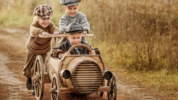 Kids push the old timey wheel barrel racer