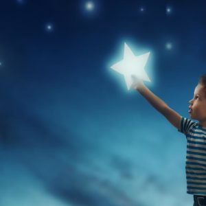 boy grasps for the stars