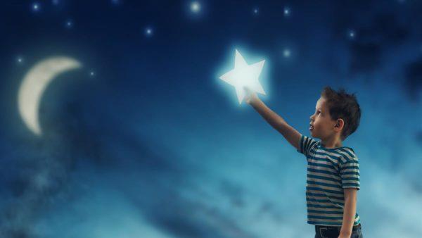 boy grasps for the stars